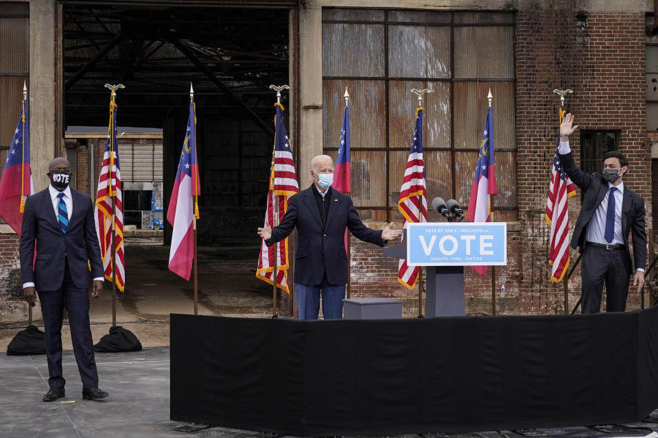 Flanked by U.S. Democratic Senate candidates the Rev. Raphael Warnock and Jon Ossoff, President-elect Joe Biden addresses a drive-in rally in Atlanta on Tuesday. (Drew Angerer/Getty Images)