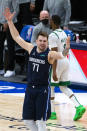 Dallas Mavericks guard Luka Doncic (77) raises his arms in the air after making a 3-point basket during the second half of an NBA basketball game against the Boston Celtics in Dallas, Tuesday, Feb. 23, 2021. (AP Photo/Sam Hodde)
