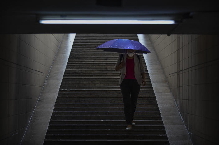 A woman wearing a face mask to protect against the coronavirus walks into the entrance of a subway station during a rainfall in Beijing, Wednesday, Aug. 5, 2020. Measures to contain the spread on a COVID-19 outbreak in China's northwestern region of Xinjiang, including locking down some communities and limiting public transport, appear to have been effective and reported case numbers have gradually fallen. (AP Photo/Mark Schiefelbein)