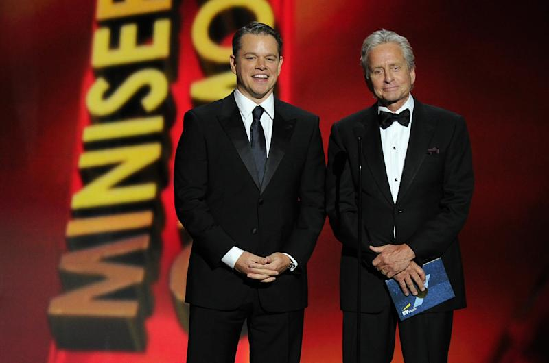 Matt Damon, left, and Michael Douglas introduce a performance by Elton John on stage at the 65th Primetime Emmy Awards at Nokia Theatre on Sunday Sept. 22, 2013, in Los Angeles. (Photo by Chris Pizzello/Invision/AP)