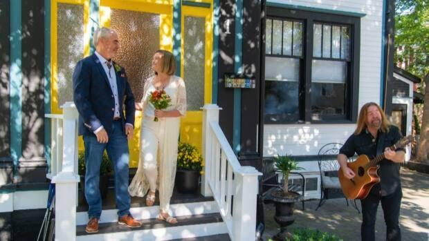 Ontario residents Lori Winsor and Brad Thorman eloped to Newfoundland and were planning to see Alan Doyle perform in concert. But when the concert was cancelled, he surprised them with a visit. (Submitted by Lori Winsor - image credit)