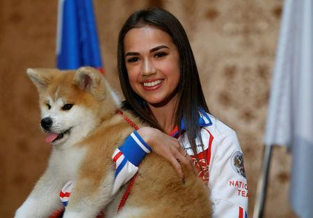 Russian figure skating gold medallist Alina Zagitova poses with an Akita Inu puppy presented to her in Moscow, Russia May 26, 2018. REUTERS/Maxim Shemetov