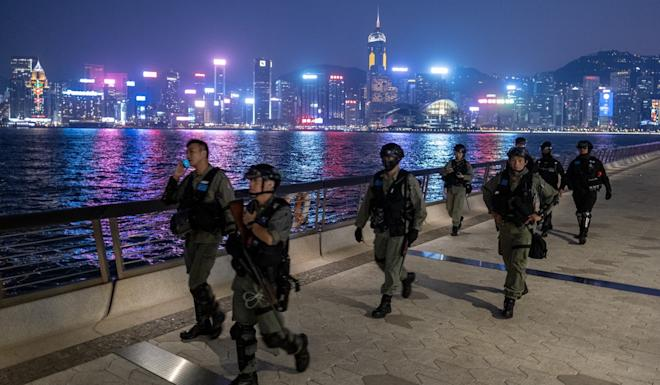 Riot police walk along a promenade in Tsim Sha Tsui. Photo: Bloomberg