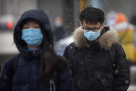 People wearing face masks to protect against the spread of the coronavirus walk along a street during a snowy morning in Beijing, Tuesday, Jan. 19, 2021. A Chinese province near Beijing grappling with a spike in coronavirus cases is reinstating tight restrictions on weddings, funerals and other family gatherings, threatening violators with criminal charges. (AP Photo/Mark Schiefelbein)