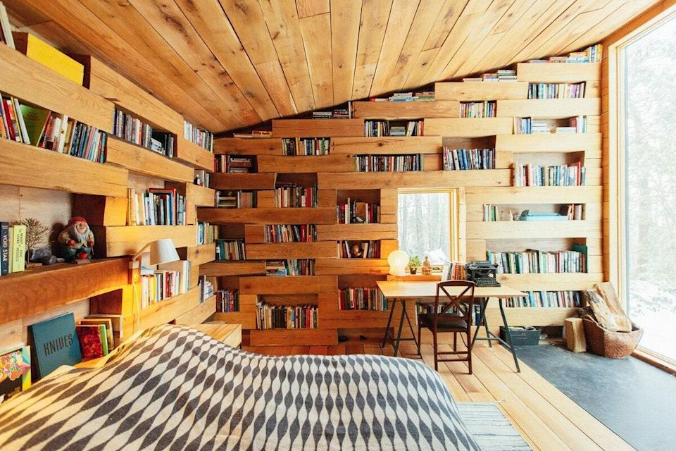 """The main house at this Airbnb two hours north of New York City is some 1,400 square feet, with two modern bedrooms; an open-plan living, dining, and kitchen area with floor-to-ceiling windows; and small bookshelves with photography, music, and architecture coffee table books. But the real draw is that it comes with a standalone one-room reading cabin, with three walls of bookshelves, a desk, a wall-to-wall window with views of the surrounding woods, a queen-sized bed for afternoon naps, and a wood-burning stove. $380, Airbnb (Starting Price). <a href=""""https://www.airbnb.com/rooms/36065640"""" rel=""""nofollow noopener"""" target=""""_blank"""" data-ylk=""""slk:Get it now!"""" class=""""link rapid-noclick-resp"""">Get it now!</a>"""