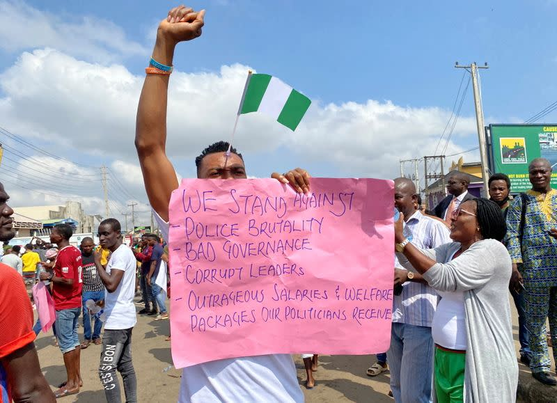 A demonstrator carries a banner during a protest demanding police reform in Lagos