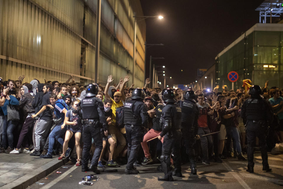 Police charge against demonstrators during clashes outside El Prat airport in Barcelona, Spain, Monday, Oct. 14, 2019. Riot police have charged at protesters outside Barcelona's airport after the Supreme Court sentenced 12 prominent Catalan separatists to lengthy prison terms for their roles in a 2017 push for the wealthy Spanish region's independence. (AP Photo/Emilio Morenatti)