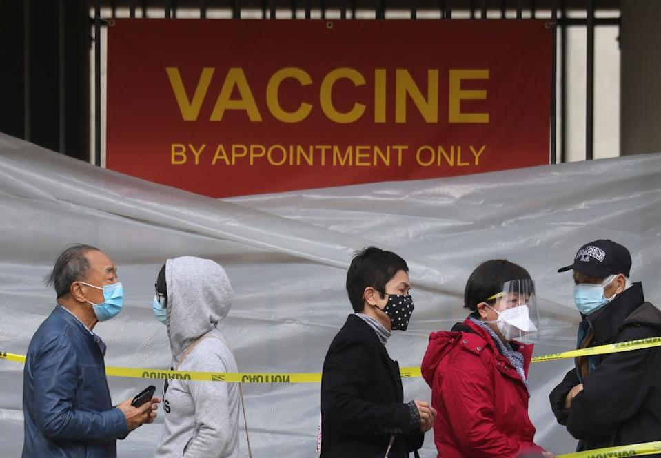 People with appointments stand in line to receive the COVID-19 vaccine at a vaccination site at Lincoln Park in East Los Angele
