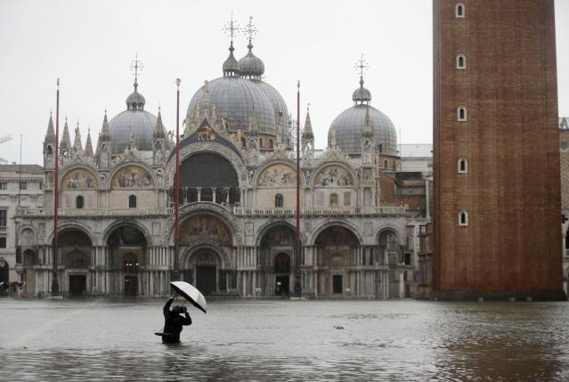 A photographer takes pictures in a flooded St. Mark's Square, in Venice, Italy, Tuesday, Nov. 12, 2019. (Photo: Luca Bruno/AP)