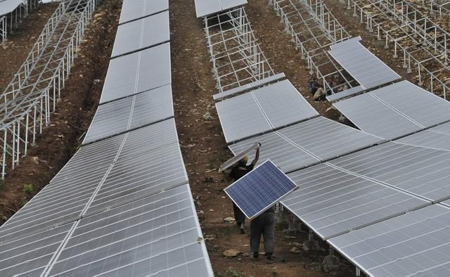 FILE PHOTO: Workers carry solar panels as they work at a solar power plant which is under construction on a hill in Wuhu