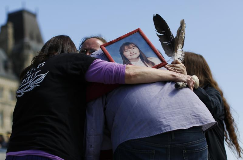 A photograph of Dauphinais is seen as participants hug during the '24 Hour Sacred Gathering of Drums' protest calling for an inquiry into missing and murdered aboriginal women, on Parliament Hill in Ottawa