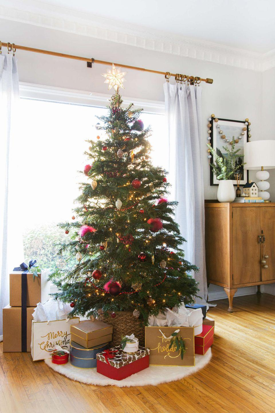 "<p>If you place your tree in front of a window, you'll be able to see it from the outside, too. Everybody wins!</p><p>See more at <a href=""https://stylebyemilyhenderson.com/blog/home-ginny-christmas"" rel=""nofollow noopener"" target=""_blank"" data-ylk=""slk:Emily Henderson"" class=""link rapid-noclick-resp"">Emily Henderson</a>.</p><p><a class=""link rapid-noclick-resp"" href=""https://www.amazon.com/Ornativity-Silver-Glitter-Design-Topper/dp/B07QDPDQRJ/ref=sr_1_1?crid=1DAICT9D376QL&dchild=1&keywords=star+christmas+tree+topper&qid=1596759876&s=home-garden&sprefix=star+christmas+tree%2Cgarden%2C173&sr=1-1&tag=syn-yahoo-20&ascsubtag=%5Bartid%7C10057.g.505%5Bsrc%7Cyahoo-us"" rel=""nofollow noopener"" target=""_blank"" data-ylk=""slk:SHOP TREE TOPPERS"">SHOP TREE TOPPERS</a> <strong><em>Star Tree Topper, $10</em></strong></p>"