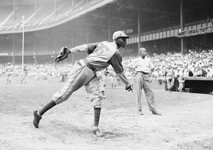 Kansas City Monarchs pitching great Leroy Satchel Paige warms up at New York's Yankee Stadium Aug. 2, 1942 for a Negro League game between the Monarchs and the New York Cuban Stars. (Matty Zimmerman / AP)