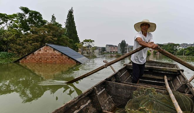 A fisherman rows his boat past a submerged house in the village of Longkou, Poyang county in Jiangxi on Thursday. Photo: AFP