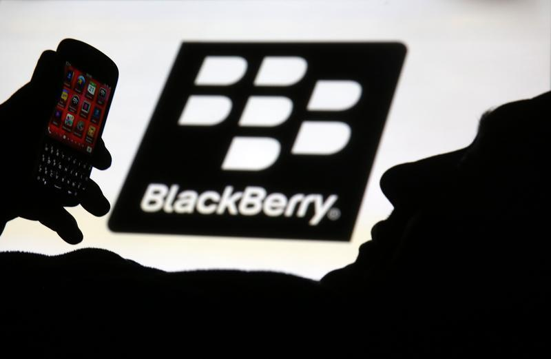 Man is silhouetted against a video screen with Blackberry logo as he pose with Blackberry Q10 in this photo illustration taken in the central Bosnian town of Zenica