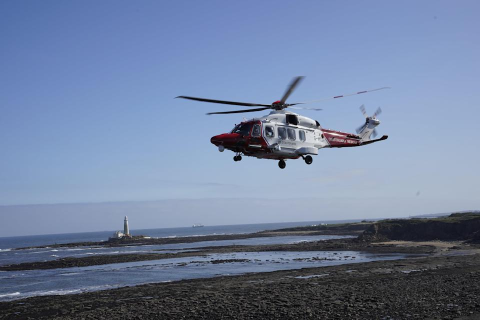 An HM coastguard helicopter lifts off to airlift a person to safety at Old Hartley near Whitley Bay (Owen Humphreys/PA) (PA Wire)