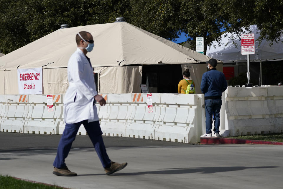 A medical worker passes a medical tent outside the emergency room at UCI Medical Center, Thursday, Dec 17, 2020, in Irvine, Calif. California health authorities reported Thursday a record 379 coronavirus deaths and more than 52,000 new confirmed cases. (AP Photo/Ashley Landis)