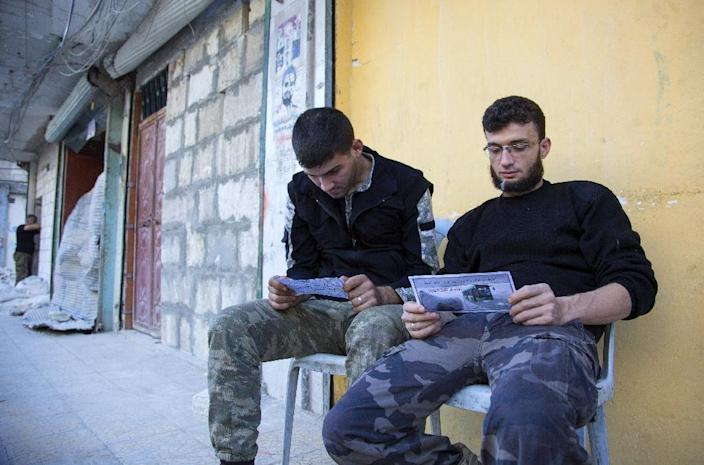 Moscow accuses rebels, seen here looking at flyers encouraging people to evacuate Aleppo, of preventing civilians from leaving (AFP Photo/Karam Al-Masri)