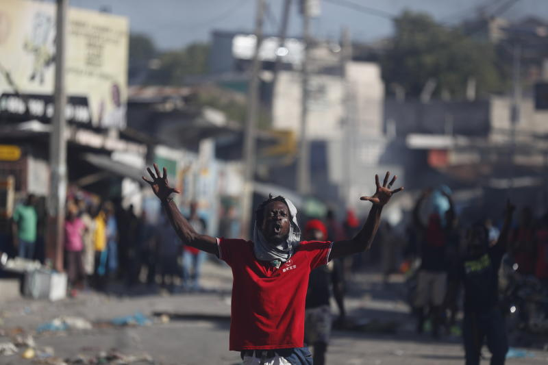 An anti-government protester shouts that Haitian President Jovenel Moise must step down, in Port-au-Prince, Haiti, Monday, Oct. 7, 2019. The country enters its fourth week of protests that have paralyzed the economy. (AP Photo/Rebecca Blackwell)