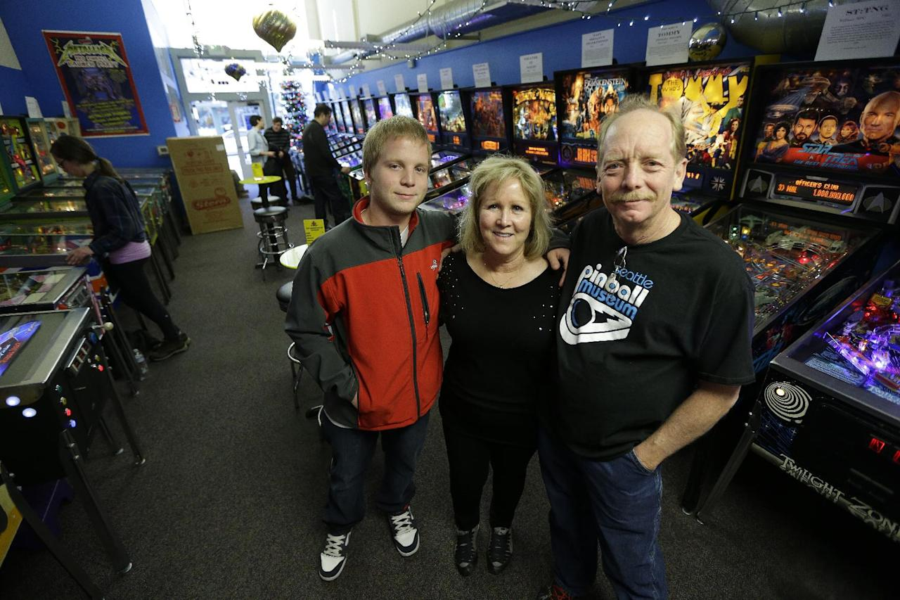 In this Dec. 16, 2013 photo, Charles Martin, right, poses for a photo with his wife Cindy, center, and their son Michael, left, on the main level of the Seattle Pinball Museum in Seattle. The Martins own and operate the museum, which allows visitors who pay the admission fee to play unlimited rounds on the machines, which range from the 1960s to modern-day games. (AP Photo/Ted S. Warren)