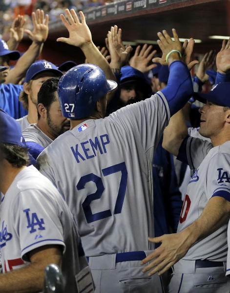 Los Angeles Dodgers Matt Kemp (17) is greeted in the dugout after scoring on a two-run home run by Juan Uribe during the first inning of a baseball game against the Arizona Diamondbacks, Tuesday, Sept. 17, 2013, in Phoenix. (AP Photo/Matt York)