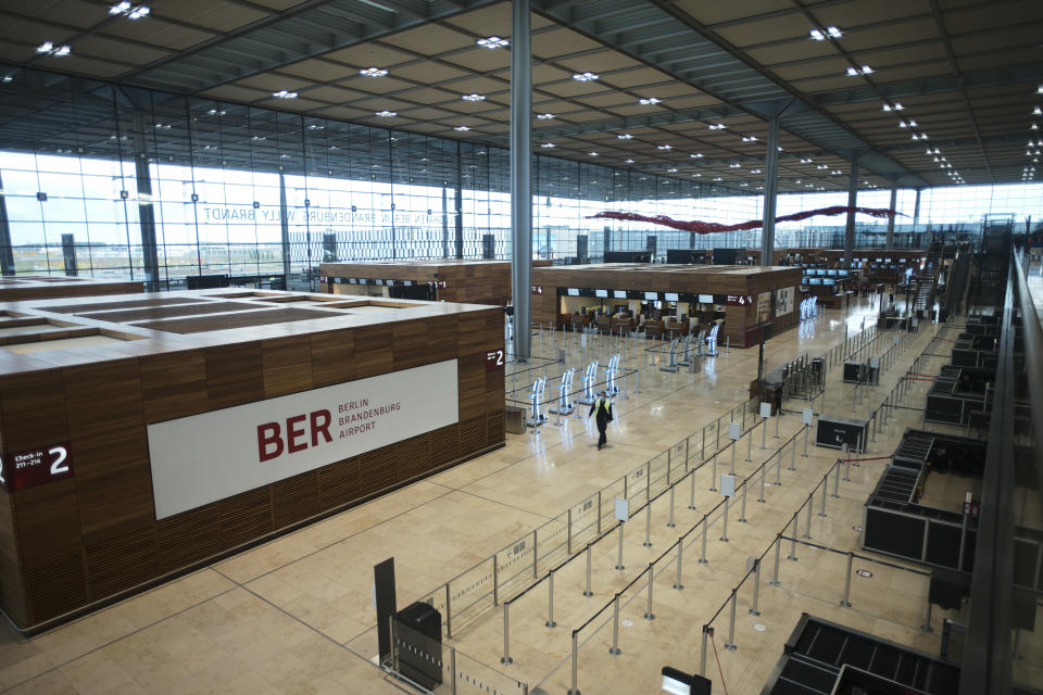 People walk through the Terminal 1 of the new Berlin-Brandenburg-Airport 'Willy Brandt' near Berlin in Schoenefeld, Germany, Tuesday, Oct. 27, 2020. After years of delays and massive cost overruns the opening of the German capital's new airport is scheduled for Saturday Oct. 31.(AP Photo/Markus Schreiber)