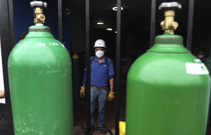 A worker wearing a mask to prevent the spread of the new coronavirus looks at two oxygen bottles before refilling them in Callao, Peru, Wednesday 3, 2020. Long neglected hospitals in Peru and other parts of Latin America are reporting shortages of Oxygen as they confront the COVID-19 pandemic. (AP Photo/Martin Mejia)