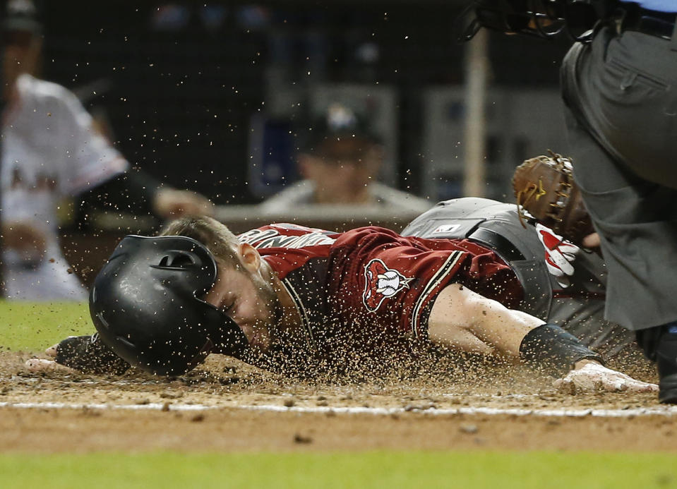 Arizona Diamondbacks' Chris Owings dives into home as Miami Marlins catcher Bryan Holaday tags him out during the fifth inning of a baseball game Wednesday, June 27, 2018, in Miami. (AP Photo/Wilfredo Lee)