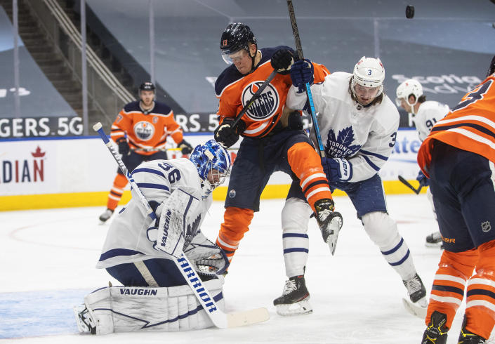 Edmonton Oilers' Jesse Puljujarvi (13) and Toronto Maple Leafs' Justin Holl (3) battle in front as goalie Jack Campbell (36) makes the save during the second period of an NHL game in Edmonton, Alberta, on Saturday, Feb. 27, 2021. (Jason Franson/The Canadian Press via AP)