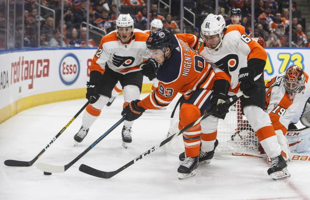 Philadelphia Flyers' Justin Braun (61) and Edmonton Oilers' Ryan Nugent-Hopkins (93) reach for the puck during the second period of an NHL hockey game Wednesday, Oct. 16, 2019, in Edmonton, Alberta. (Jason Franson/The Canadian Press via AP)