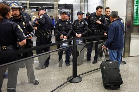 Police redirect travelers after the security check point was closed due to protests in Terminal 4 at San Francisco International Airport in San Francisco, California, U.S., January 28, 2017. REUTERS/Kate Munsch