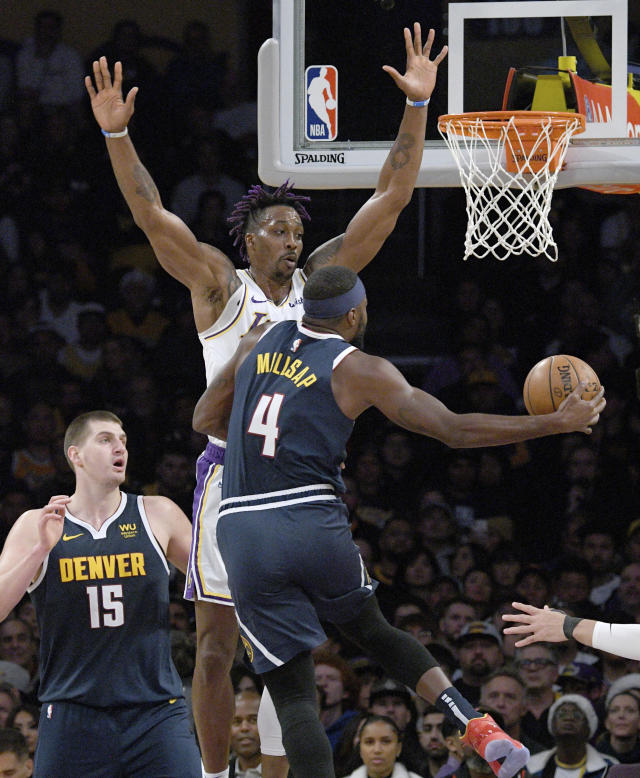 Los Angeles Lakers center Dwight Howard, center, defends the basket against Denver Nuggets forward Paul Millsap, right, during the first half of an NBA basketball game Sunday, Dec. 22, 2019, in Los Angeles. (AP Photo/Michael Owen Baker)