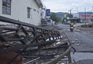 A motorist rides past a building damaged by an earthquake in Mamuju, West Sulawesi, Indonesia, Saturday, Jan. 16, 2021. Damaged roads and bridges, power blackouts and lack of heavy equipment on Saturday hampered Indonesia's rescuers after a strong and shallow earthquake left a number of people dead and injured on Sulawesi island. (AP Photo/Azhari Surahman)