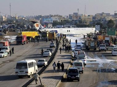 Aging Iranian passenger aircraft carrying 144 crash-lands and skids onto busy highway, only two injured