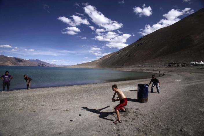 FILE- In this July 22, 2011 file photo, children play cricket near Pangong Lake, near the India-China border in Ladakh, India. While the recent troop standoff in a remote Himalayan desert spotlights a long-running border dispute between China and India, the two emerging giants are engaged in a rivalry for global influence that spreads much farther afield. (AP Photo/Channi Anand, File)