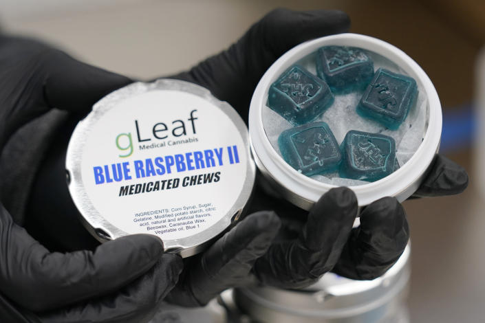 A worker displays a tin of Green Leaf medicated chews are stacked up at the company's plant in Richmond, Va., Thursday, June 17, 2021. The date for legalizing marijuana possession is drawing near in Virginia, and advocacy groups have been flooded with calls from people trying to understand exactly what becomes legal in July. (AP Photo/Steve Helber)