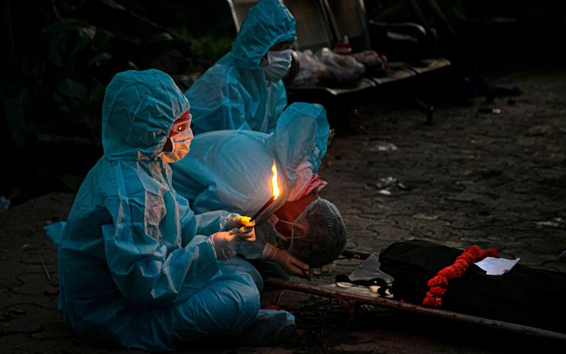 Relatives in personal protective equipment perform rituals during the cremation of a person who died of Covid-19 in Gauhati, India - AP
