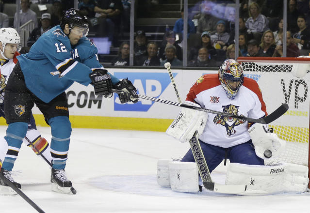 Florida Panthers goalie Roberto Luongo, right, blocks a shot next to San Jose Sharks' Patrick Marleau (12) during the first period of an NHL hockey game on Tuesday, March 18, 2014, in San Jose, Calif. (AP Photo/Marcio Jose Sanchez)