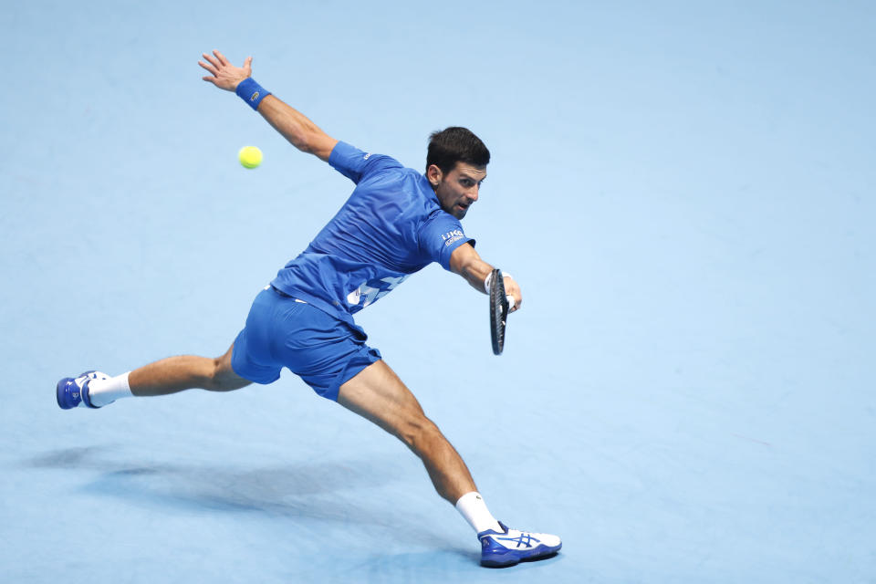 Novak Djokovic of Serbia returns the ball to Dominic Thiem of Austria during their semifinal match at the ATP World Finals tennis tournament at the O2 arena in London, Saturday, Nov. 21, 2020. (AP Photo/Frank Augstein)