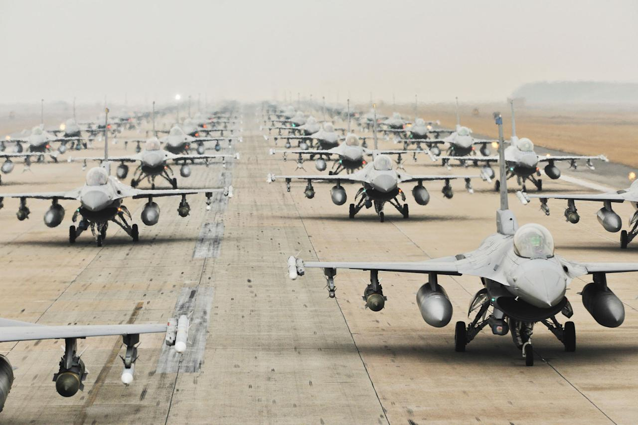 "Various aircrafts demonstrate an ""Elephant Walk"" as they taxi down a runway during an exercise at Kunsan Air Base, South Korea. The exercise showcased the aircrews' capability to quickly and safely prepare an aircraft for a wartime mission (Brittany Y. Auld/USAF/Rex Features)"
