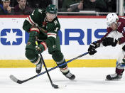 Minnesota Wild's Mikko Koivu (9), of Finland, passes the puck away from Colorado Avalanche's Valeri Nichushkin (13), of Russia, during the first period of an NHL hockey game Sunday, Feb. 9, 2020, in St. Paul, Minn. (AP Photo/Hannah Foslien)