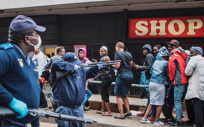 A South African policeman points his pump rifle to disperse a crowd of shoppers in Yeoville, Johannesburg - MARCO LONGARI/AFP