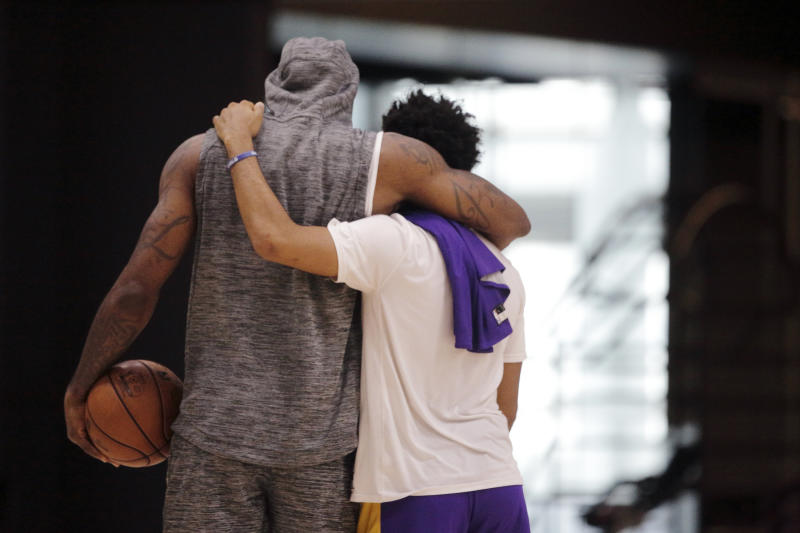 Los Angeles Lakers forward LeBron James, left, and guard Quinn Cook embrace at the end of NBA basketball practice in El Segundo, Calif., Thursday, Jan. 30, 2020. The Lakers held their second practice Thursday, while they continue to grieve for former player Kobe Bryant. (AP Photo/Damian Dovarganes)