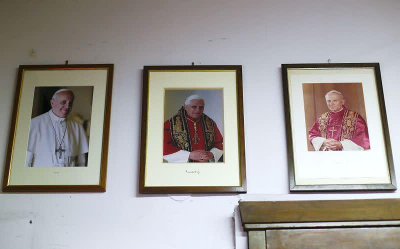 FILE PHOTO: Framed pictures of Pope Francis, Pope Benedict XVI and Pope John Paul II hang on the wall inside the Gammarelli tailor shop in Rome
