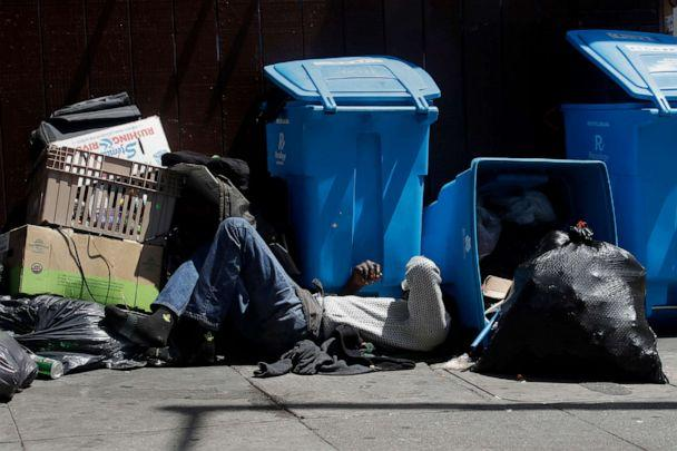 PHOTO: A homeless man sleeps in front of recycling bins and garbage on a street corner in San Francisco, Aug. 21, 2019. (Jeff Chiu/AP)