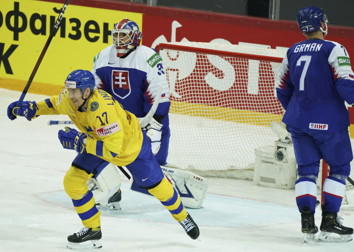 Par Lindholm of Sweden, left, celebrates goal during the Ice Hockey World Championship group A match between the Sweden and Slovakia at the Olympic Sports Center in Riga, Latvia, Sunday, May 30, 2021. (AP Photo/Oksana Dzadan)