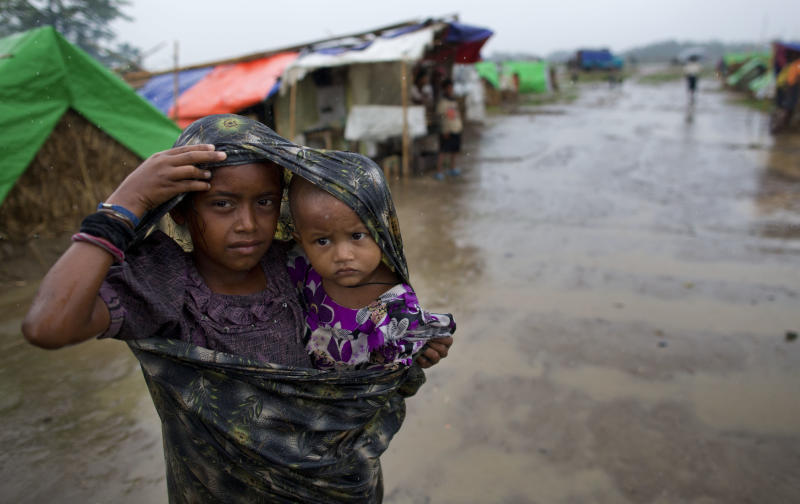 Internally displaced Rohingya girl walks with a sibling in rain at a makeshift camp for Rohingya people in Sittwe, northwestern Rakhine State, Myanmar, ahead of the arrival of Cyclone Mahasen, Tuesday, May 14, 2013. The U.N. said the cyclone, expected later this week, could swamp makeshift housing camps sheltering tens of thousands of Rohingya. Myanmar state television reported Monday that 5,158 people were relocated from low-lying camps in Rakhine state to safer shelters. But far more people are considered vulnerable. (AP Photo/Gemunu Amarasinghe)
