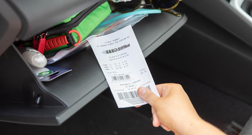 Man holds Lotto Strike ticket which delivered one player a life-changing prize