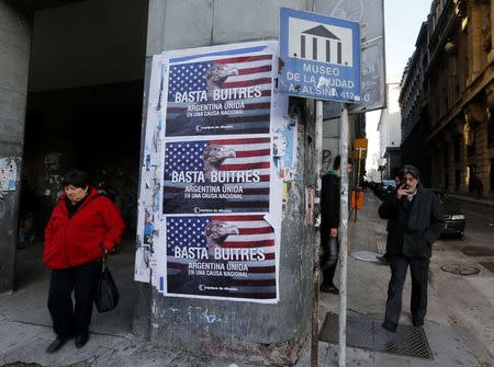 """Pedestrians stand next to posters that read """"Enough vultures, Argentina united for a national cause"""" in Buenos Aires"""