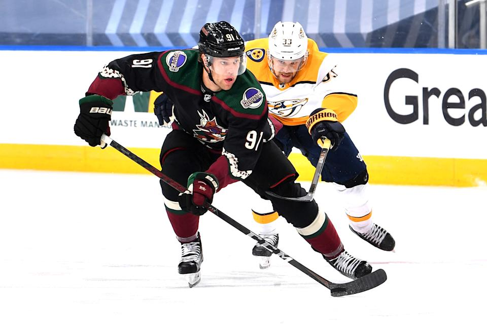 EDMONTON, ALBERTA - AUGUST 05: Taylor Hall #91 of the Arizona Coyotes skates the puck away from Viktor Arvidsson #33 of the Nashville Predators during the first period of Game Three of the Western Conference Qualification Round at Rogers Place on August 05, 2020 in Edmonton, Alberta. (Photo by Andy Devlin/NHLI via Getty Images)